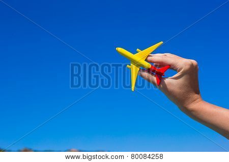 Small homemade plane in hand on background of blue sky