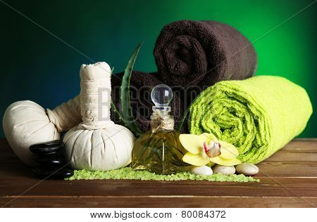 Spa treatments with orchid flowers on wooden table on colorful background