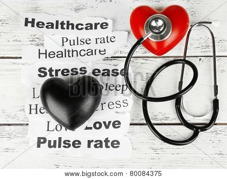 Decorative heart with stethoscope on paper notes, on wooden background