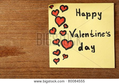 Valentines day note on wooden background
