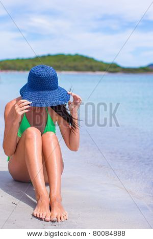 Young beautiful girl relaxing at tropical beach during summer vacation