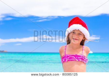 Little adorable girl in red Santa hat at tropical beach