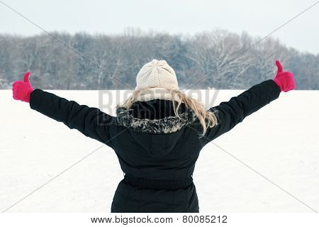 Woman In Snow Showing Her Back And Facing Forest With Thumbs Up Hands Raised
