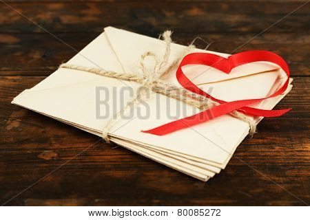Stack of letters with ribbon in heart shape on rustic wooden table background
