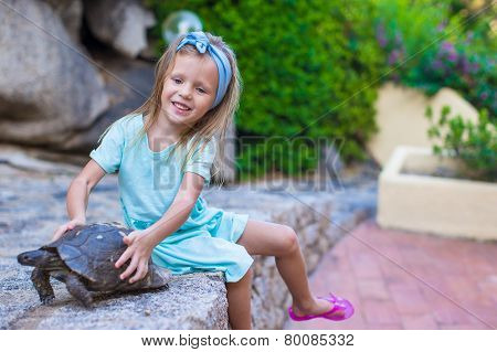 Little adorble happy girl with small turtle outdoors