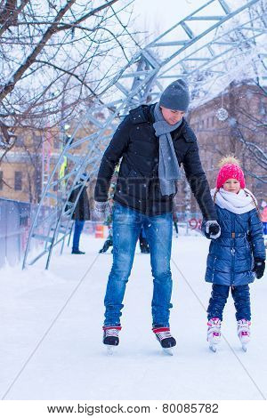 Young father and adorable little girl on skating rink outdoor