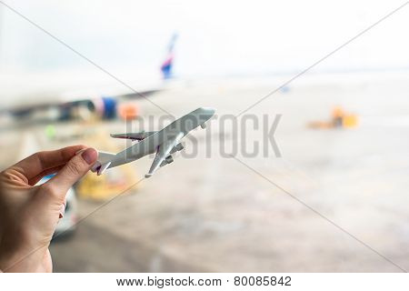 Close up hand holding an airplane model at airport