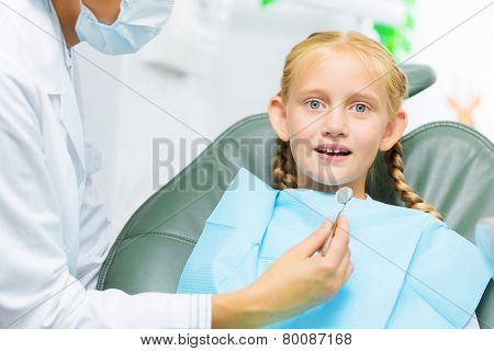 Cute smiling girl in at dentist sitting in armchair