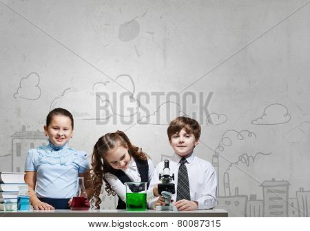 Three cute children at chemistry lesson making experiments