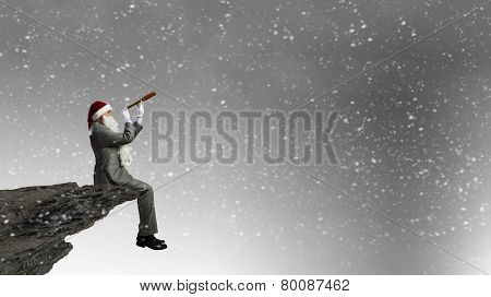 Businessman in Santa hat sitting on edge and looking in spyglass