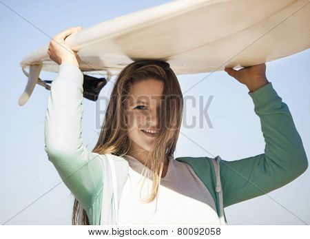 Tenage girl in the beach and holding a surfboard over her head