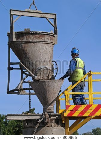 Worker pours cement into the well