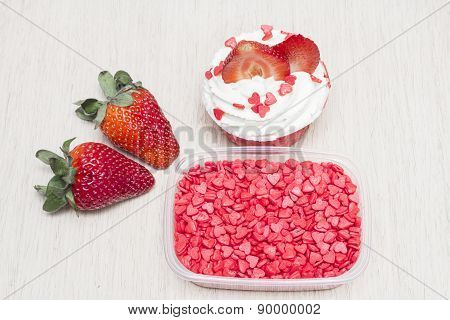 Cupcakes with white cream with strawberries and decorations