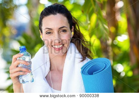 Fit beautiful brunette looking at camera while listening music on a sunny day