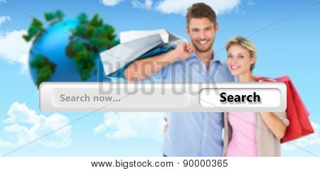 Attractive young couple holding shopping bags against blue sky