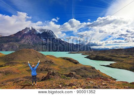 Strong winds in the Chilean Patagonia. National Park Torres del Paine, Lake Pehoe. The woman raised her hands with delight the beauty of nature
