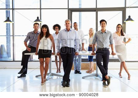 Coworkers posing to camera in meeting room