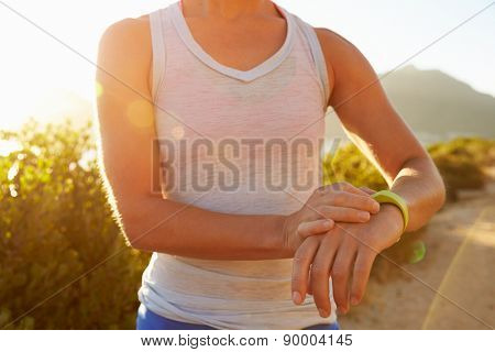 Young woman checking time on her sports watch