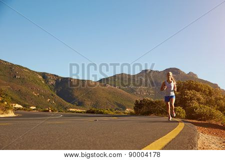 Young woman running on an empty road