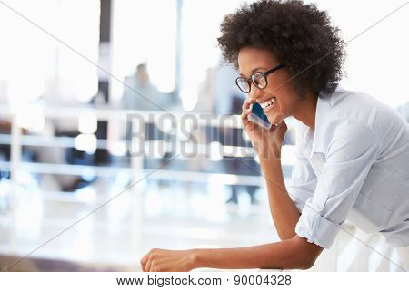 Portrait of smiling woman in office talking on phone
