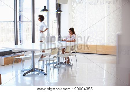 Two women working with digital tablet in empty meeting room