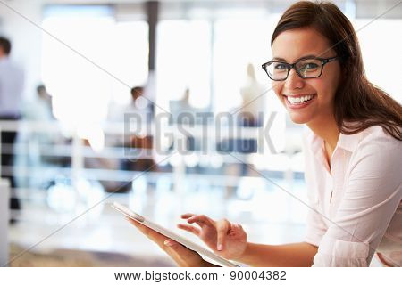 Portrait of smiling woman in office with tablet