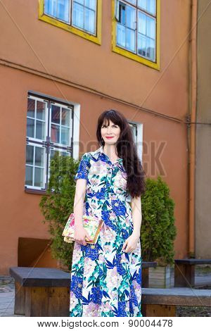 Beautiful Woman In Long Dress Posing Over Old Building