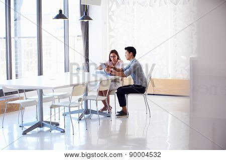 Two people working with digital tablet in empty meeting room