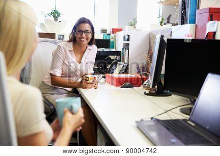 Two women having a coffee break at work