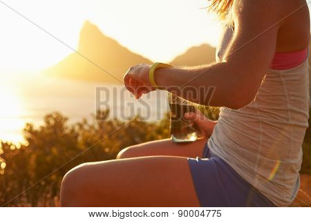 Young woman checking her sports watch
