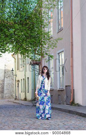 Young Woman In Long Dress Walking In Old Town Of Tallinn