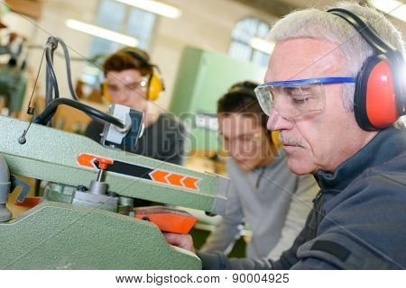 Experienced carpenter teaching two teenage boys