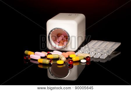 Colorful pills over dark background. Red Spotlight above