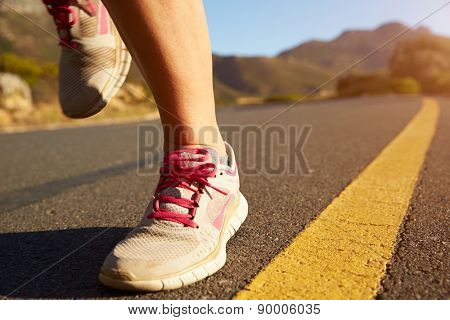 Cropped shot of female jogger running on an empty road