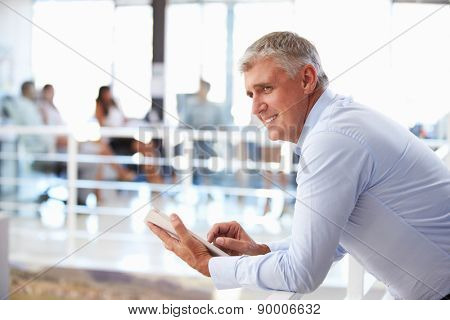 Portrait of middle aged man in office using tablet