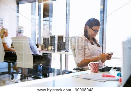 Woman using smart phone,phone at her desk in an office