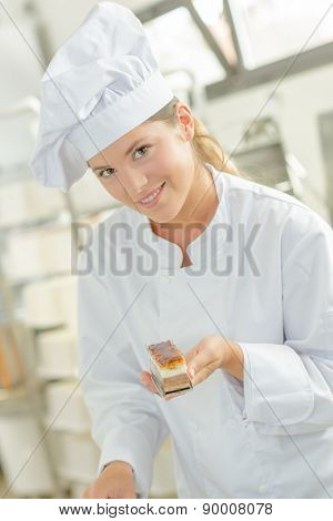 Baker holding one of her desserts