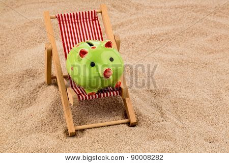 deckchair with piggy bank on the sandy beach. symbol photo for costs in travel, vacation, holiday. save on holiday