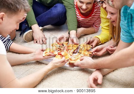 food, leisure and friendship concept - close up of happy teenage friends eating pizza at home