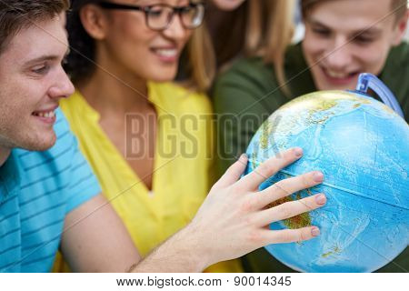 education, geography subject, high school, teamwork and people concept - group of smiling students looking at globe