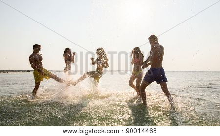 friendship, sea, summer vacation, holidays and people concept - group of happy friends having fun on summer beach