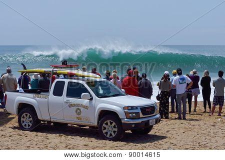 Spectators And Lifeguards Observing Huge Surf