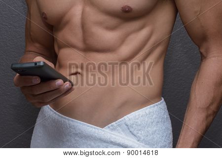 Closeup Abs Of Man Wrapped In Towel As He Texts On Phone