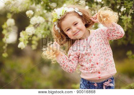 Portrait of little girl outdoors in a lush garden.