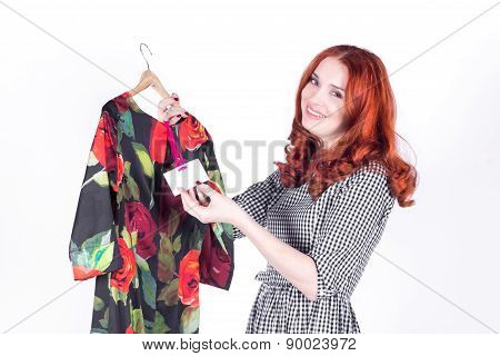 Attractive woman looks at the price of the dress and enjoys a low price