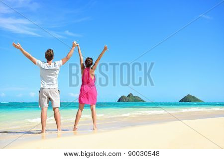 Summer beach happy free couple cheering on travel holiday. Back view of young people with arms raised to the sky showing success and freedom on Lanikai beach, Oahu, Hawaii, USA with Mokulua Islands.