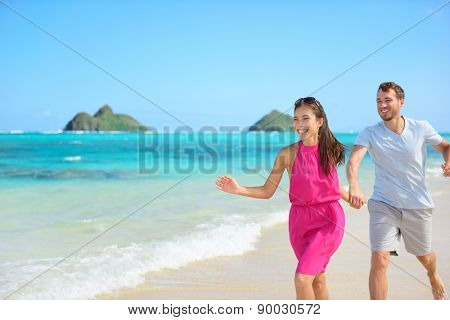 Beach couple happy running having fun on Hawaii. Romantic couple cheerful and full of happiness on travel vacation on Lanikai beach, Oahu, Hawaii, USA with Mokulua Islands. Asian woman, Caucasian man poster