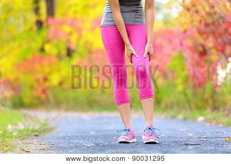 Muscle injury of female sports runner thigh. Woman running muscle strain injury in thigh. Closeup of runner touching leg in muscle pain outside in fall forest.