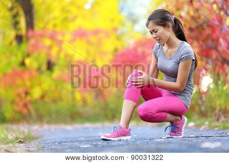 Sports running knee injury on woman in pain. Female runner with pain from sprain knee. Close up of legs, muscle and knee outdoors in late summer autumn forest.
