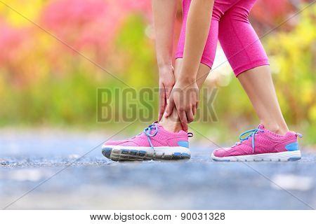 Running sport injury - twisted broken ankle. Female athlete runner touching foot in pain due to sprained ankle.